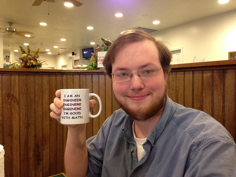 Sam Reed holds a congratulatory coffee mug after officially becoming an engineer